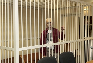 Human rights activist Ales Belyatsky sits in a guarded cage in a courtroom in Minsk